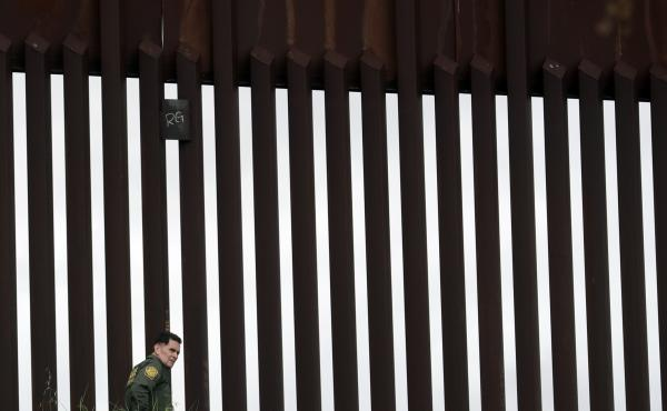 A border patrol agent walks along a border wall separating Tijuana, Mexico, from San Diego in March. The Trump Administration has proposed a number of changes that would restrict asylum claims.