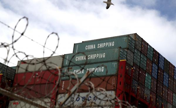 Shipping containers sit on a Hong Kong-based container ship at the Port of Oakland in California last month. The cost of the tariffs is likely to ripple through the global supply chains that make up much of the trade between the U.S. and China.