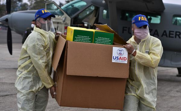 Foreign aid takes many forms — and Trump and Biden have differing perspectives. Above: Members of the Honduran Armed Forces carry a box of COVID-19 diagnostic testing kits donated by the United States Agency for International Development and the Interna