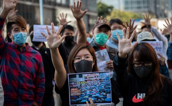 People gather in support of pro-democracy protesters during a lunch break rally in the Kwun Tong area in Hong Kong on Wednesday. Hong Kong has been battered by months of mass rallies and violent clashes between police and protesters who are demanding dire