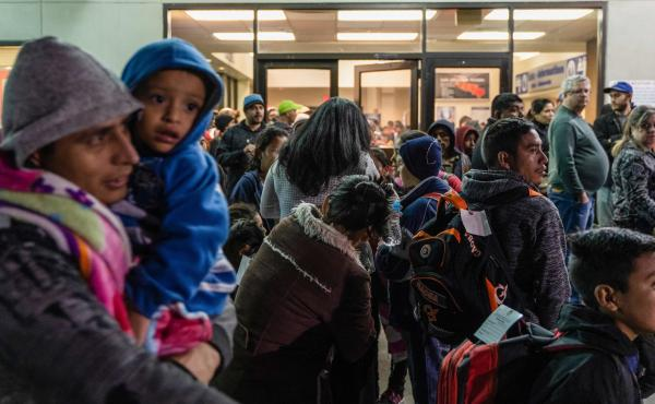 Asylum seekers stand at a bus stop after they were dropped off by Immigration and Customs Enforcement at the Greyhound bus station in El Paso, Texas on Dec. 23.