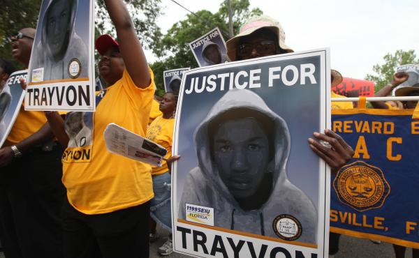 Protesters hold up signs at a march and rally for slain Florida teenager Trayvon Martin in Sanford, Fla., on March 31, 2012.