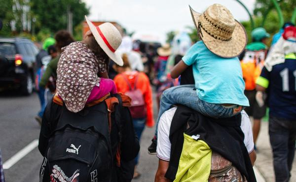 """Children are carried on the shoulders of Central American migrants heading to the U.S. along the road between Metapa and Tapachula, Mexico, on April 12. President Trump has called for measures to close what he calls the asylum """"loophole"""" amid a spike in b"""