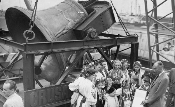 A group of former displaced persons helps load the Freedom Bell aboard a Navy transport vessel in Brooklyn, N.Y., on Oct. 9, 1950. One of the children, Eva Zandler, 8, originally from Poland, presents a scroll — to be enshrined in the Freedom Bell's tow