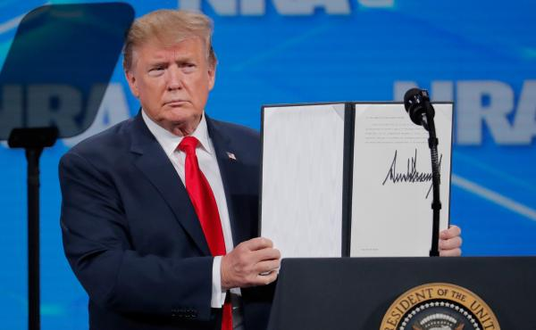 President Trump holds up an executive order he signed at an NRA event Friday, announcing that the United States will drop out of the Arms Trade Treaty that was signed during the Obama administration.
