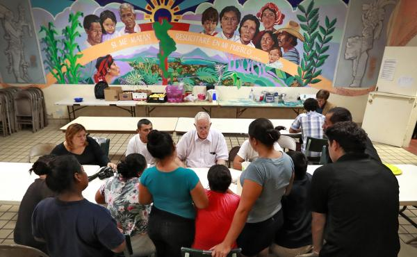 Ruben Garcia (center), director of the Annunciation House, speaks with migrant parents on June 26, 2018, in El Paso, Texas.