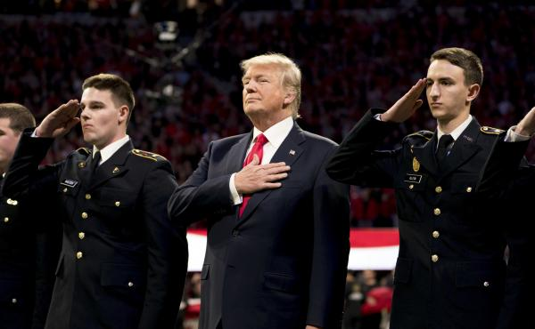 President Trump stands, with his hand over his heart, on the field for the national anthem before the start of the NCAA National Championship football game in January.