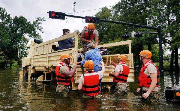 Texas National Guardsmen assist residents affected by flooding onto a military vehicle on Sunday in Houston.