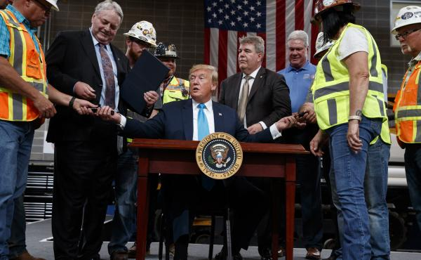 President Trump hands out pens after signing an executive order aimed at making it easier for companies to pursue oil and gas pipeline projects. The president addressed an audience at the International Union of Operating Engineers International Training a