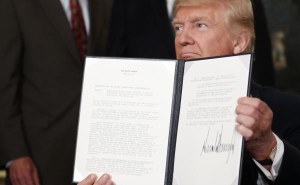 President Trump holds up a signed memorandum calling for a trade investigation of China at the White House on Monday.