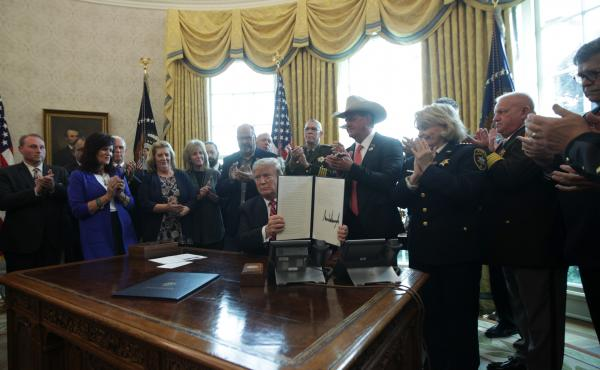 President Trump shows the executive veto of the national emergency resolution in the Oval Office of the White House Friday.
