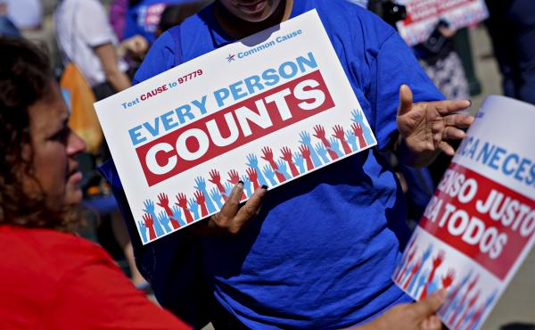 A demonstrator hands out a sign about the 2020 census outside the U.S. Supreme Court in Washington, D.C., in 2019. The Census Bureau is projecting the first set of census numbers won't be ready until February, Trump administration attorneys told a federal