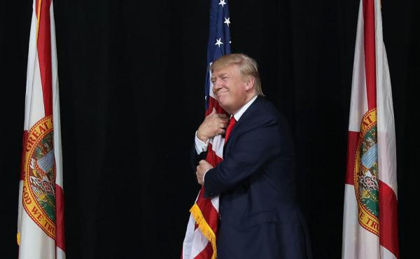 Donald Trump hugs the American flag at a campaign rally in Tampa, Fla., on Oct. 24.