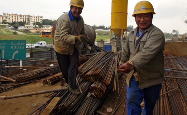 Chinese construction workers carry reinforcing rods on a building site in Algiers, Algeria.