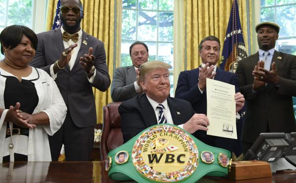 President Donald Trump, center, pardons Jack Johnson, boxing's first black heavyweight champion, during an event in the Oval Office of the White House on May 24. Trump is joined by, from left: Linda Haywood; Deontay Wilder; Keith Frankel; Sylvester Stallo