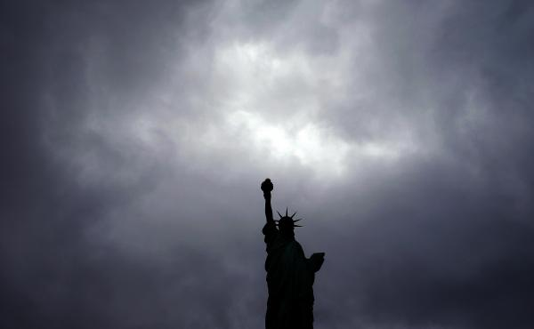 The Statue of Liberty stands tall as dark clouds cover the New York sky.