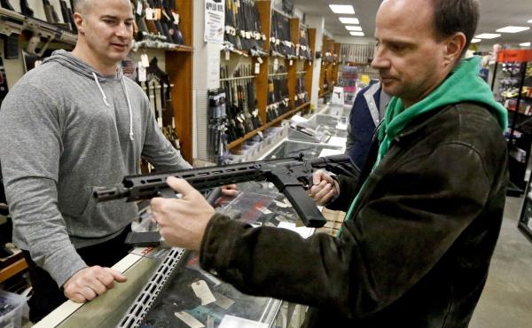 Wes Morosky, owner of Duke's Sport Shop. left, helps Ron Detka as he shops for a rifle at his store in New Castle, Penn.
