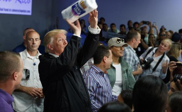 President Trump tosses paper towels into a crowd as he hands out supplies Tuesday in Guaynabo, Puerto Rico, where he went to survey hurricane damage.