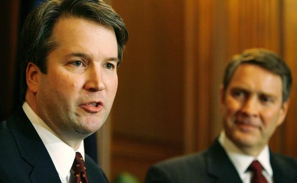 Brett Kavanaugh (left) speaks in 2006 when he was a nominee for the D.C. Circuit Court of Appeals. Then-Senate Majority Leader Bill Frist of Tennessee looks on.