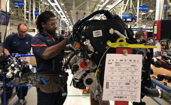 Tremaine Smalls (center) attaches parts to an engine at Volvo's plant in Ridgeville, S.C. The automaker has shifted its exports to Europe as the result of the U.S. trade war with China.