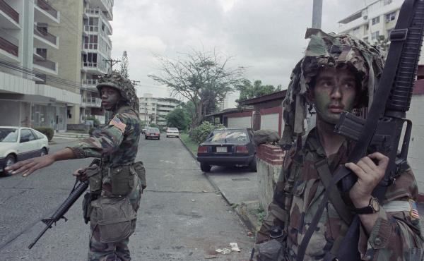 U.S. soldiers direct traffic outside the residence of the Peruvian ambassador to Panama, right rear, in Panama City on Jan. 9, 1990. In December 1989, U.S. President George H.W. Bush sent thousands of troops to Panama to arrest the country's leader, Manue