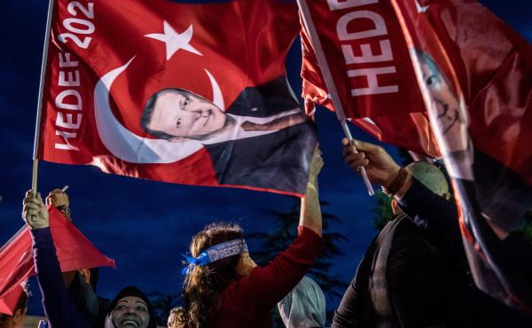 Supporters of Turkey's President Recep Tayyip Erdogan gather in front of the Huber Presidential Palace, where he delivered a victory speech. Preliminary results indicate Erdogan has avoided a runoff.
