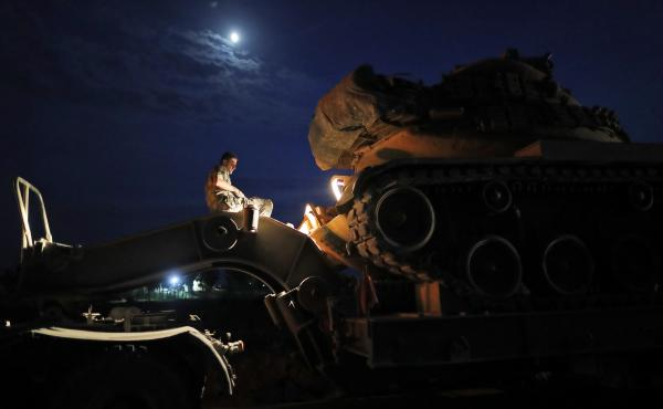 A Turkish army officer prepares to unload a tank from a truck to its new position on the Turkish side of the border between Turkey and Syria, in Sanliurfa province, southeastern Turkey, on Tuesday.