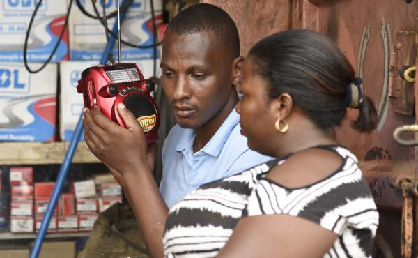 People listen to the radio as the results of the presidential elections are announced in Kireka, Uganda, in February. Many rural Ugandans don't have Internet access, and the radio is a central source of news — and platform for citizens' opinions.