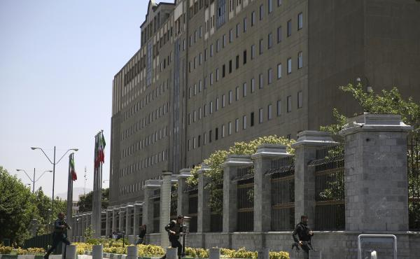 Police officers run to take position around Iran's parliament building in Tehran after an assault by several attackers. Four attackers reportedly reached the building's interior, and an explosion was heard, although it was unclear whether it was a suicide