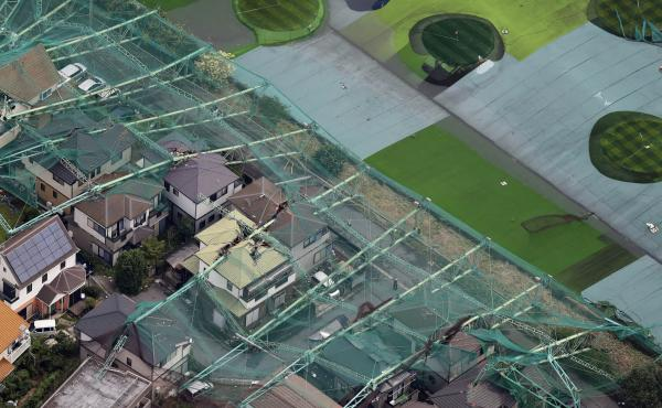 Houses damaged by the collapse of the perimeter netting of a golf training field because of strong winds from Typhoon Faxai are seen in Ichihara, east of Tokyo, on Monday.