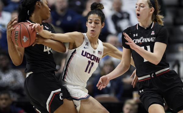 At the American Athletic Conference tournament semifinals earlier this month in Uncasville, Conn., Cincinnati's Andeija Puckett, left, looks to pass to Sam Rodgers, right, under pressure from Connecticut's Kia Nurse. Connecticut is the first overall seed