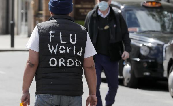 """A man with """"flu world order"""" written on his back walks in London on Tuesday, as the U.K. continues its lockdown. The U.K. is doubling the length of its worker furlough program, citing the need to help employees when the economy reopens."""