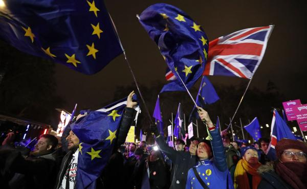 Anti-Brexit demonstrators react after the results of the vote on British Prime Minister Theresa May's Brexit deal were announced in Parliament square in London on Tuesday. British lawmakers have rejected Prime Minister Theresa May's Brexit deal by a huge