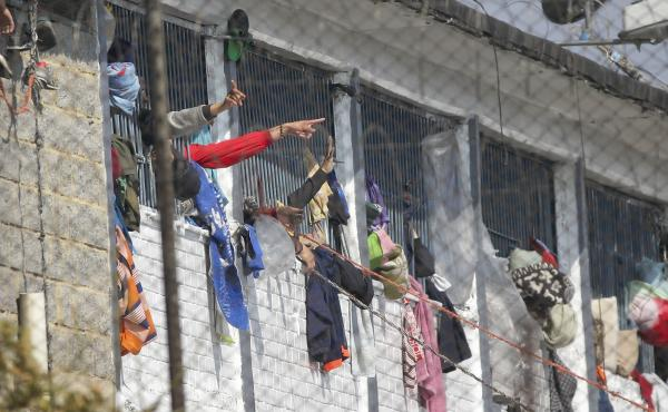 Inmates point from inside the La Modelo facility in Bogotá, Colombia, on Sunday. Violence broke out in the prison out of inmates' fears that prison guards are not doing enough to prevent coronavirus inside overcrowded prisons.