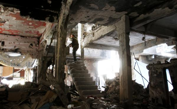 A man stands on a staircase inside a demolished building in the Yarmouk Palestinian refugee camp in the Syrian capital, Damascus, on Monday.