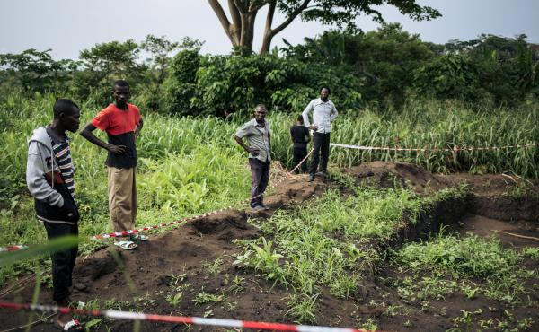 Survivors of an attack in the western village of Bongende, in the Democratic Republic of the Congo, stand next to what is said to be a mass grave containing the bodies of 100 people killed during days of violence in the region in December 2018.