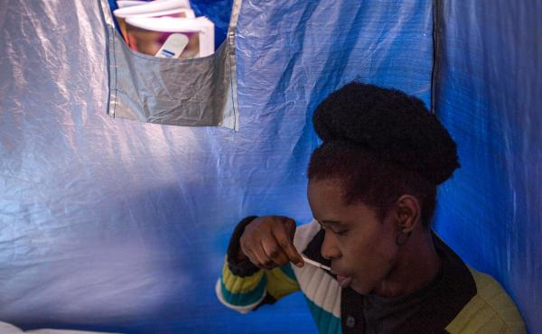 A woman in Johannesburg, South Africa, uses an HIV kit that tests for antibodies in oral fluids.