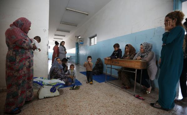 Displaced Kurdish and Arab women, who fled from violence after a Turkish offensive in northeastern Syria, sit with their children at a public school used as shelter where they now live in Hasakah, Syria.
