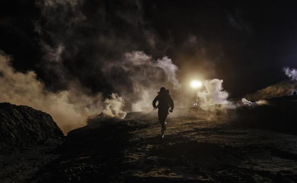 Migrants run as tear gas is thrown by U.S. Customs and Border Protection agents to the Mexican side of the border fence after they climbed the fence to get to San Diego from Tijuana, Mexico.