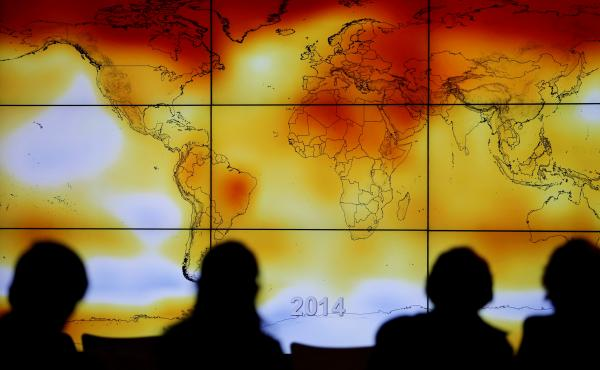 Participants look at a world map showing climate anomalies during the World Climate Change Conference 2015 in France. A draft government report on climate, which was leaked ahead of publication, says the U.S. is already experiencing the consequences of gl