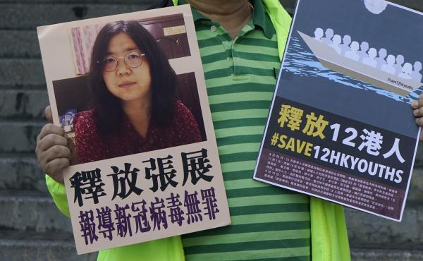 A pro-democracy activist holds placards with the picture of Chinese citizen journalist Zhang Zhan outside the Chinese central government's liaison office, in Hong Kong, Monday. Activists demand the release of Zhang, as well as the 12 Hong Kong activists d