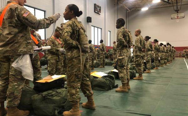 Recent Army basic combat training graduates have their temperatures taken as they arrive at Fort Lee, Va., on March 31, after being transported using sterilized buses from Fort Jackson, S.C. The Army says it will delay basic training due to COVID-19.
