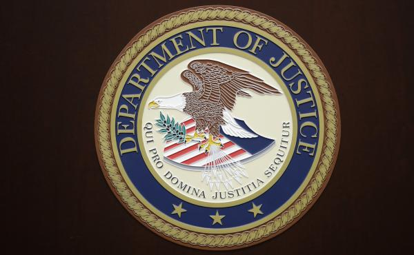 The U.S. Department of Justice logo is seen on a podium in Baltimore, last year.