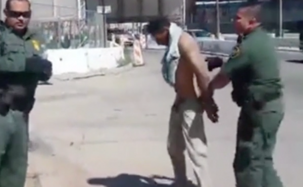 A screenshot of a video showing U.S. Border Patrol agents attempting to instruct an injured man to cross the U.S. border into Mexico, apparently violating international laws.