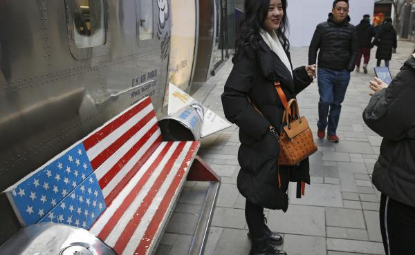 Chinese shoppers spend their time next to a bench painted with the U.S. flag at the capital city's popular shopping mall in Beijing. During trade talks this week, the two sides face potentially lengthy wrangling over technology and the future of their eco