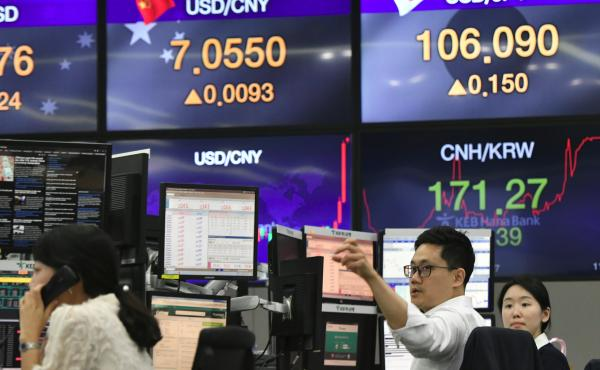 Currency dealers monitor exchange rates at the KEB Hana Bank in Seoul, South Korea. China's currency and the U.S. stock market stabilized Tuesday, after a dramatic drop the day before.