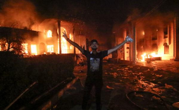 An Iraqi protester stands flashing the victory gesture outside the burning headquarters of the Iranian Consulate in Basra on Sept. 7.