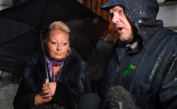 Charlotte Charles, the mother of teenage motorcyclist Harry Dunn, who was killed in a collision with an SUV driven by U.S. citizen Anne Sacoolas, stands beside her husband, Bruce Charles, as they discuss the case. Dunn's family is suing Sacoolas, who has