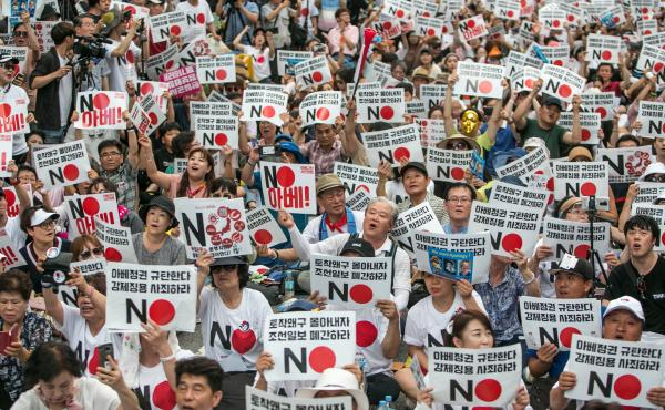 Protesters hold placards reading 'No Abe!' earlier this month during a demonstration against Japan's removal of South Korea from a list of trusted trading partners in Seoul.
