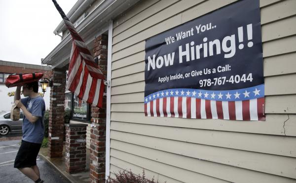 A sign advertising job openings hangs outside a restaurant in Middleton, Mass., last month. At 4.3 percent unemployment, the jobs rate is near the point that most economists deem full employment.